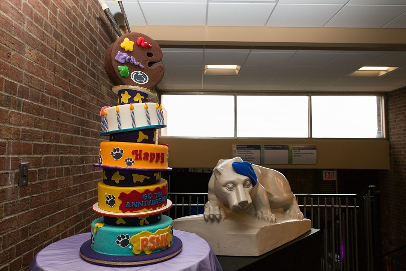 Penn State New Kensington 60th anniversary cake next to statue