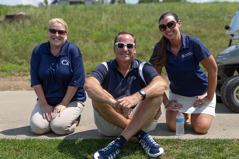 Three alumni society members at golf outing