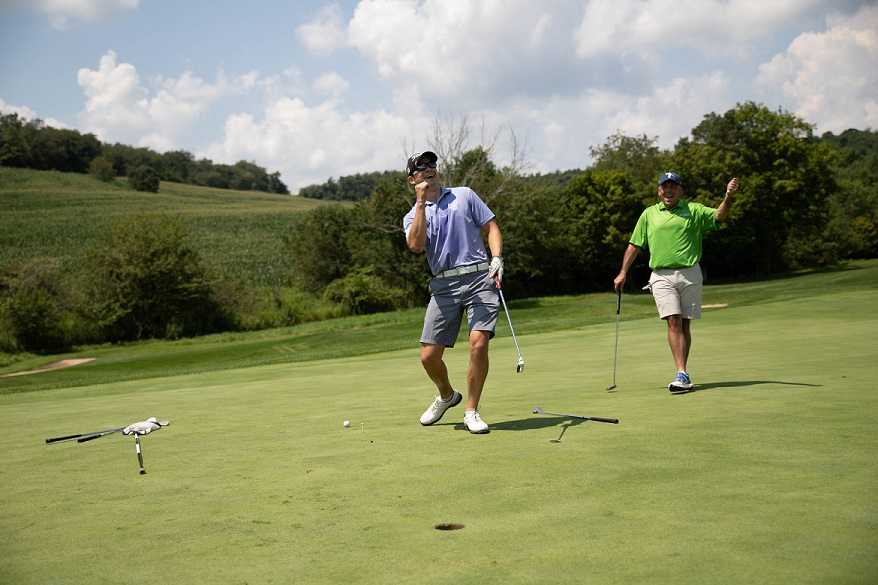 Two golfers celebrate putt on golf course