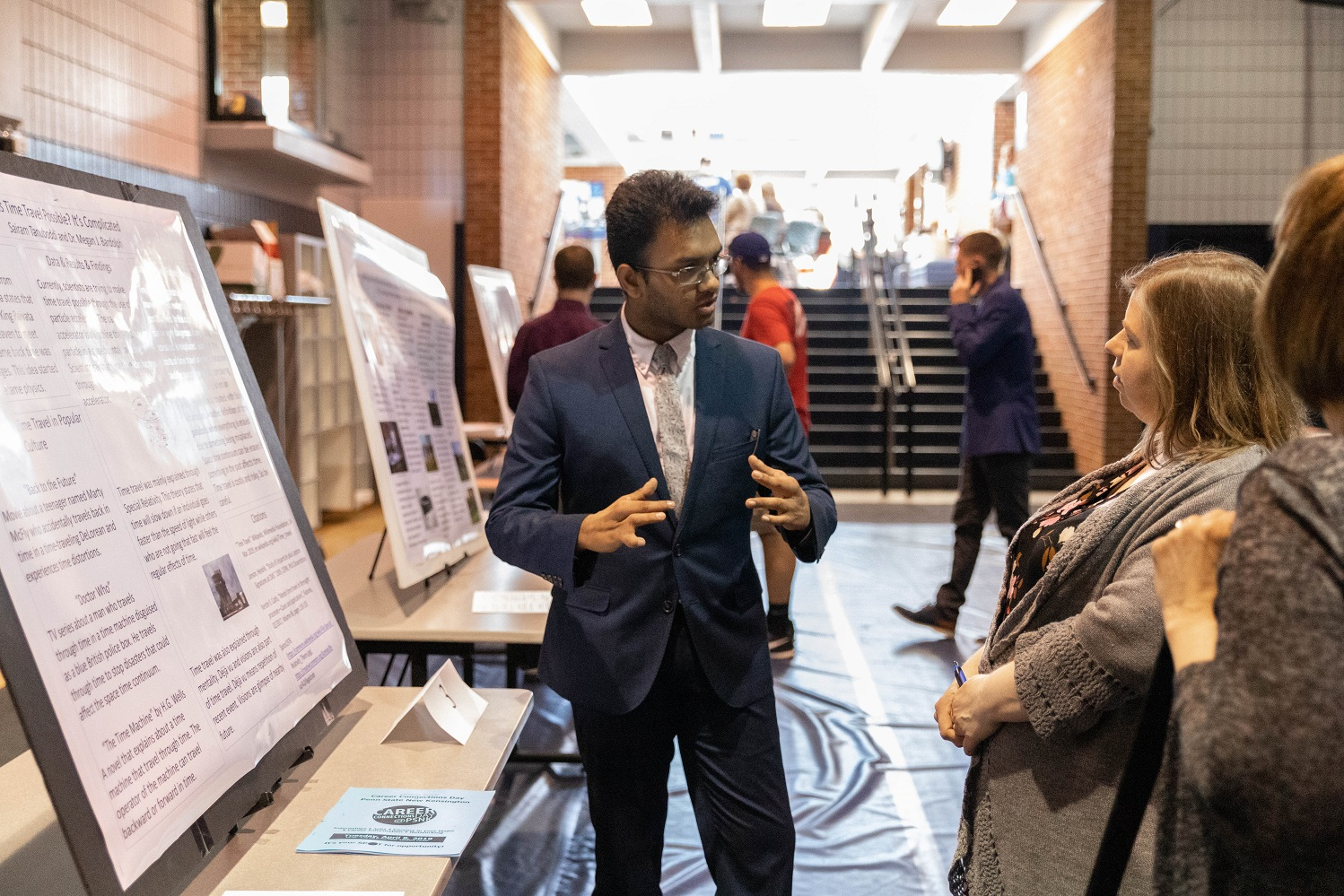 Male student presents research project to two females