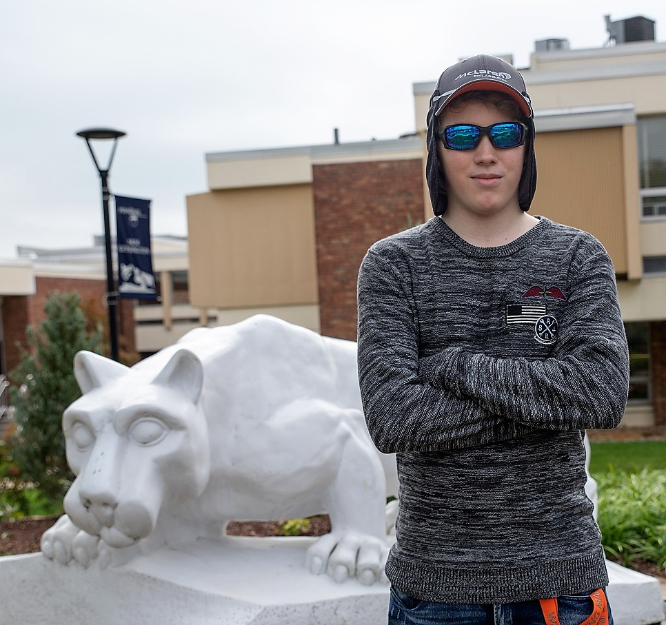 Mackinly Adams stands by lion statue