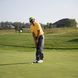 Golfer putts at golf outing