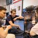 Three male students look at autonomous wheelchair