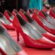 Two rows of red high heels on table