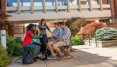 Seven students gathered around a table socializing