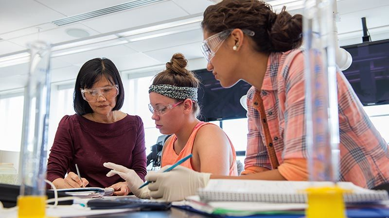 Female professor explains something to two female students during Chemistry Lab