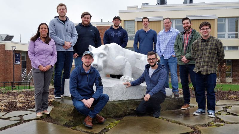 Penn State New Kensington BET students and faculty member stand by lion statue