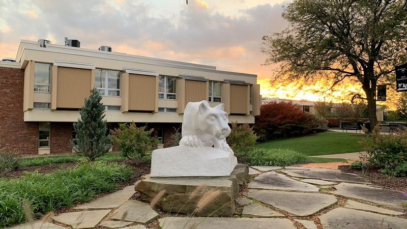 Nittany lion statue in foreground with campus buildings in background