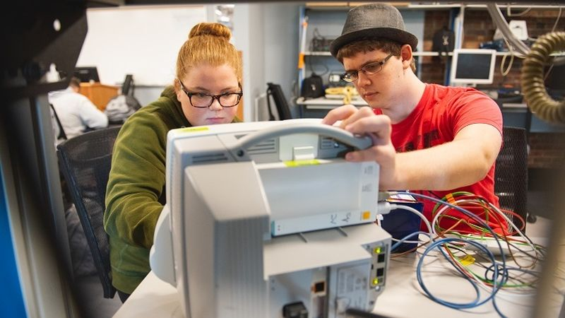 Two students work on hospital equipment in lab