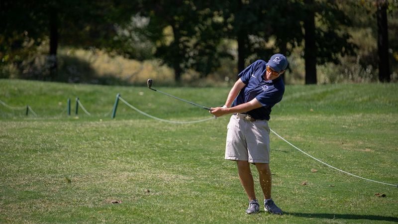 Golfer hits ball on course