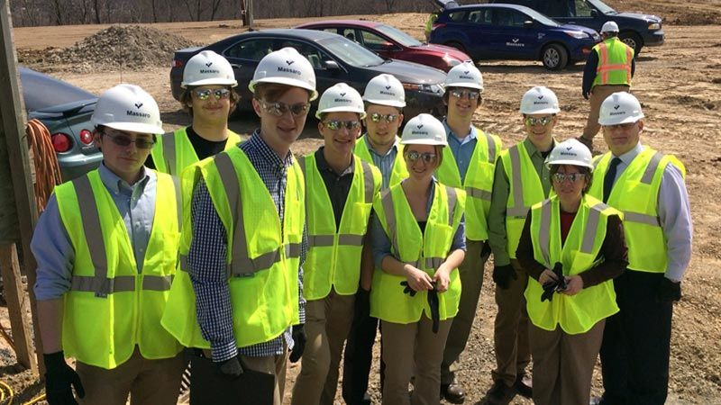 GREAT Program students and staff wear bright yellow vests and white hard hats while visiting a Massaro construction site