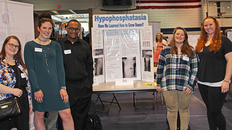 5 radiological sciences students stand in front of their poster at the annual Research & Creative Expo