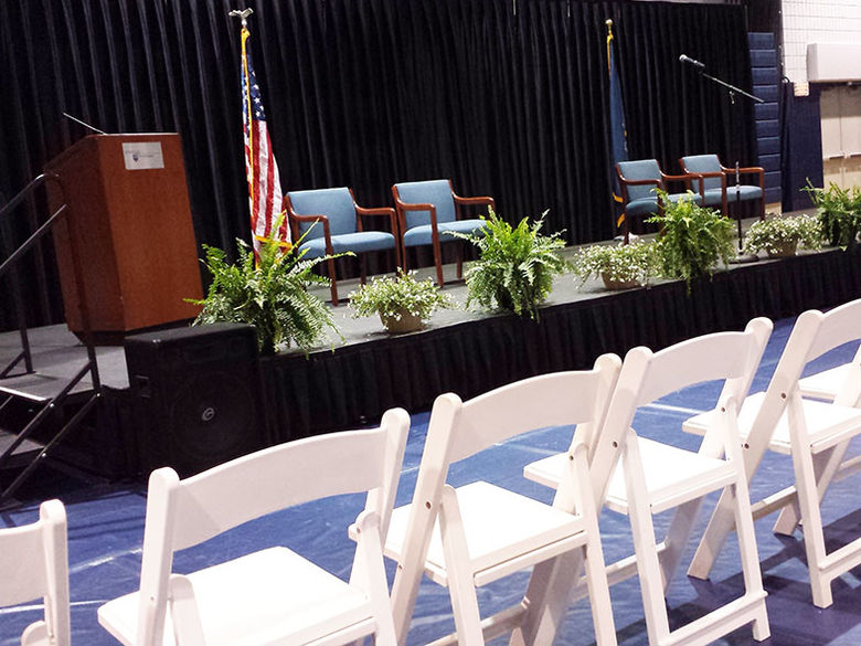 Chairs, podium, and stage set up in the gym for commencement