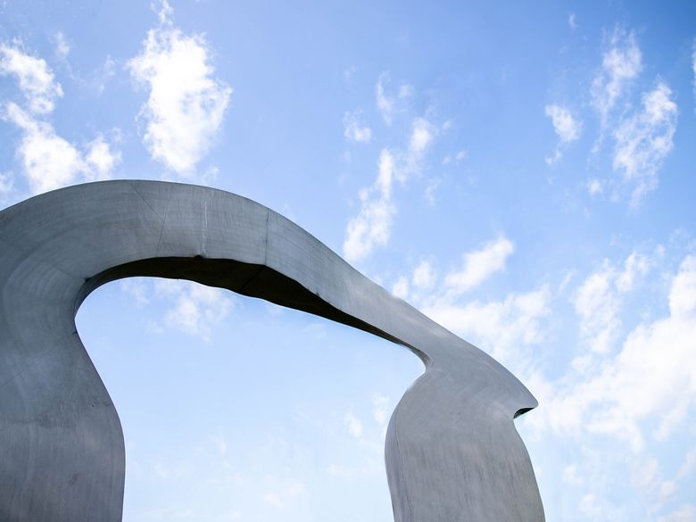 Alcoa Arch statue and sky with clouds