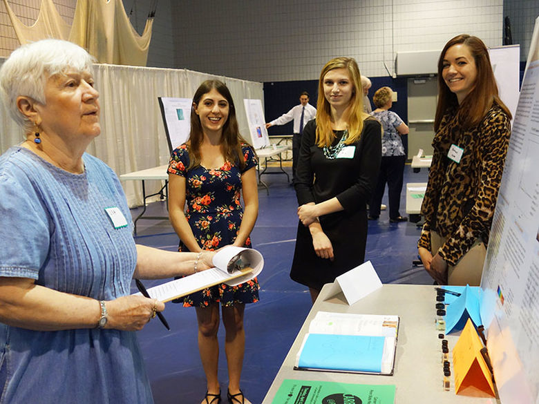 A judge reviews a poster presentation, while three female students provide additional insight