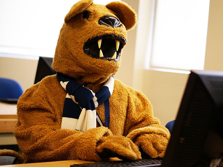 The Nittany Lion mascot looks up information on a computer in a classroom