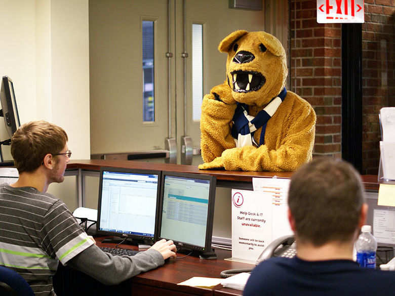 Two service desk consultants provide assistance to the Nittany Lion mascot.