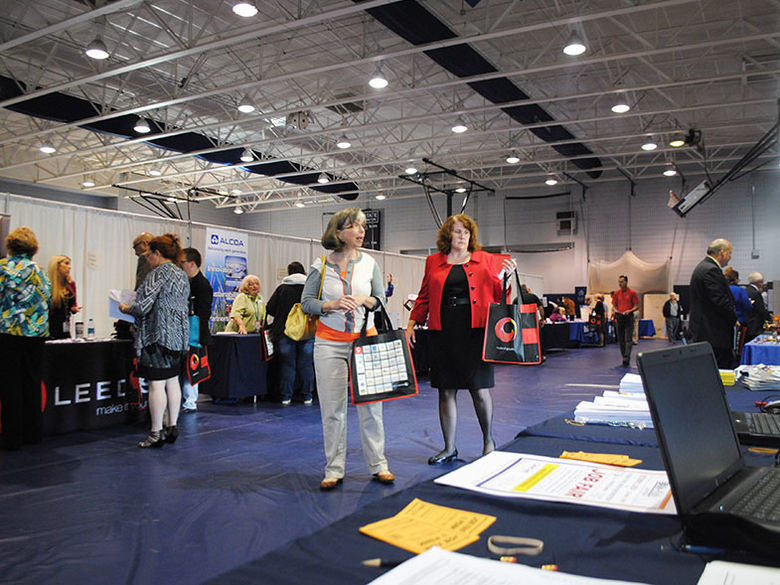 Various booths set up by companies in the gym during the annual Career Fair