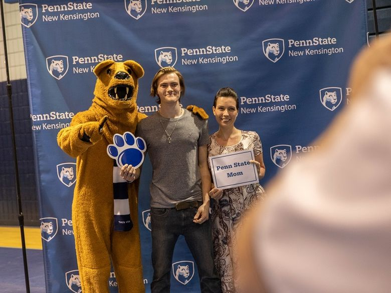 Mother and son stand with Nittany Lion mascot