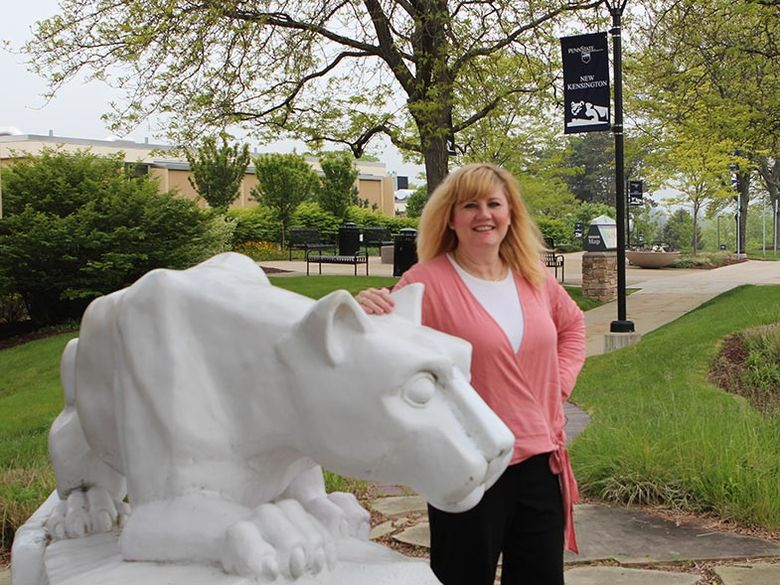 Mary, the campus registrar, stands beside the lion shrine