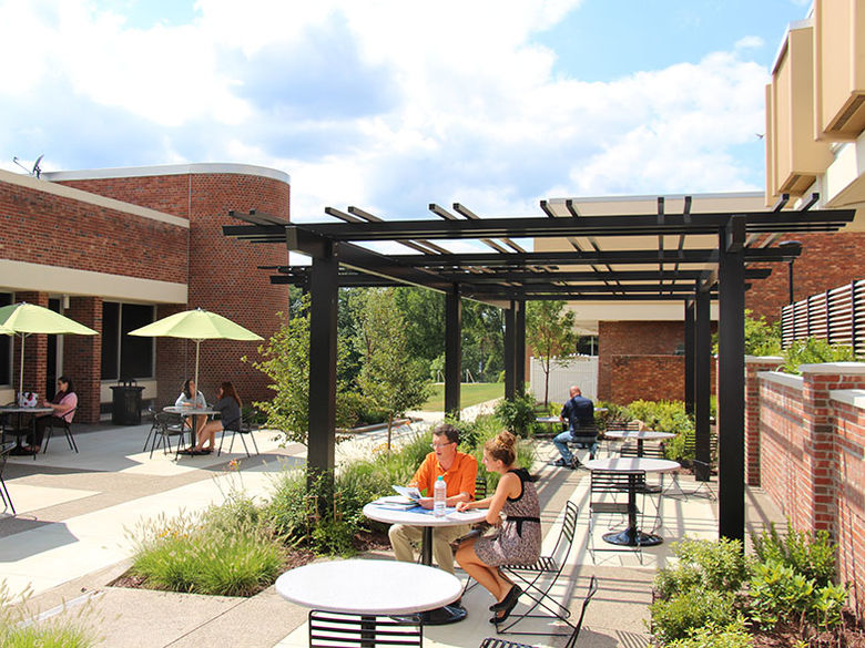 Campus courtyard with students and staff seated around tables and taking in some sun