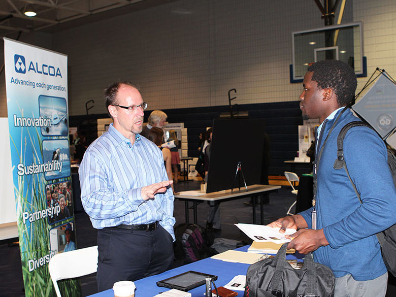 A corporate recruiter meets with an individual at a Career Fair