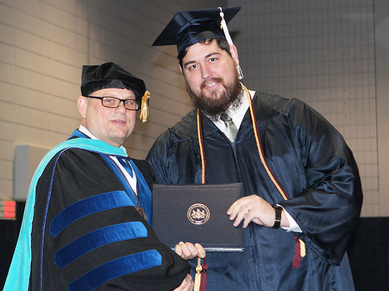 A new graduate receives his diploma from the Chancellor during a commencement ceremony
