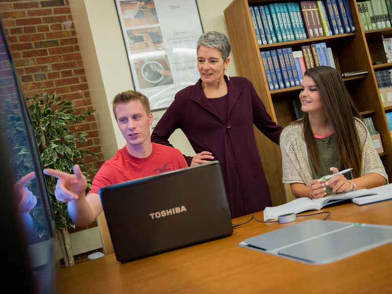 Two students share their research with a faculty member
