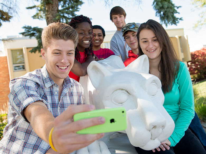 A group of students take a selfie at the campus lion shrine