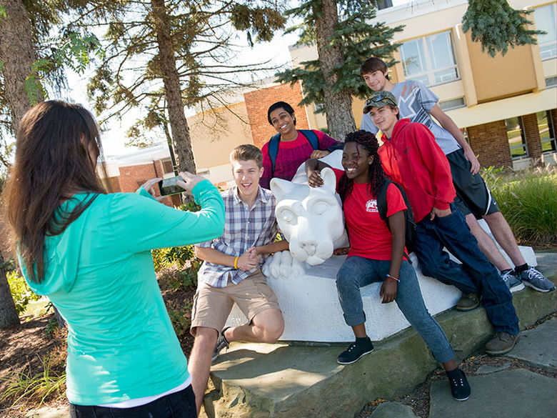 Students gather around the campus Lion Shrine while another student takes a photo of the group.