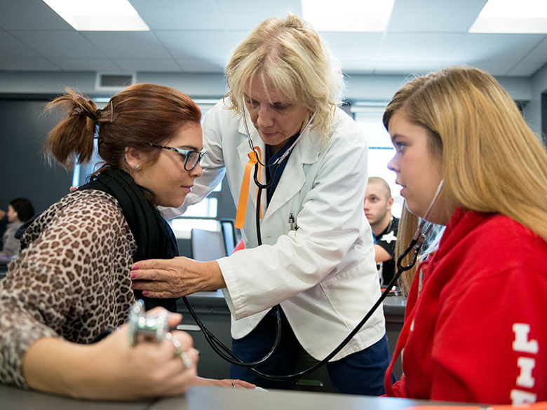 The campus nurse uses a stethoscope to listen to a student's heart