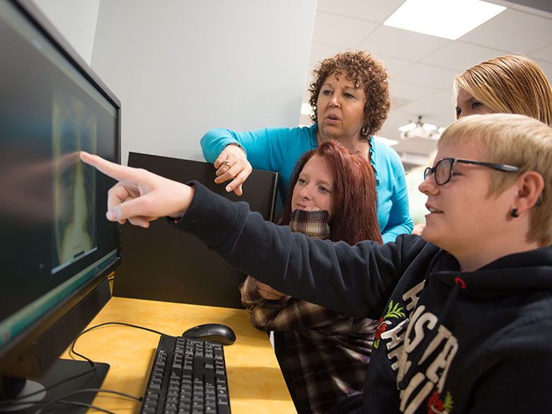 Radiological Sciences students and their instructor examine an x-ray on a computer screen