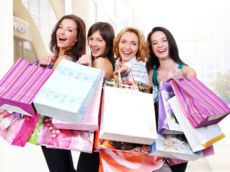 Four women holding many shopping bags