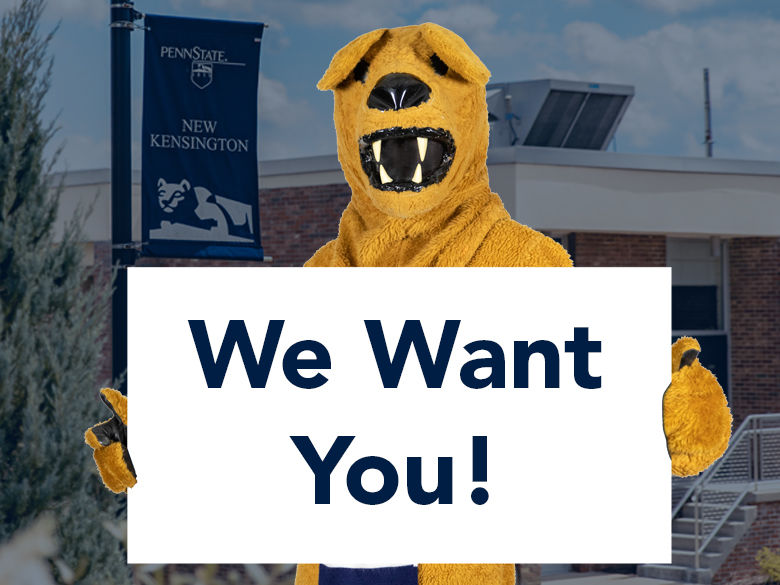 "Nittany Lion holds ""We Want You"" sign."