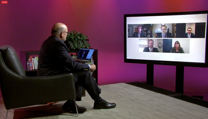 Kevin Snider sits and looks at virtual panelists on television screen