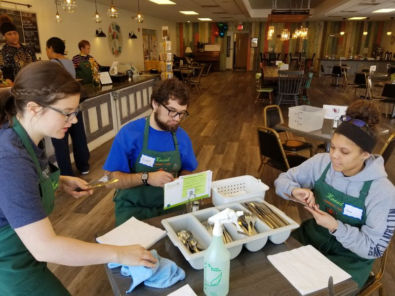 Student volunteers organize silverware at a table at Knead Cafe