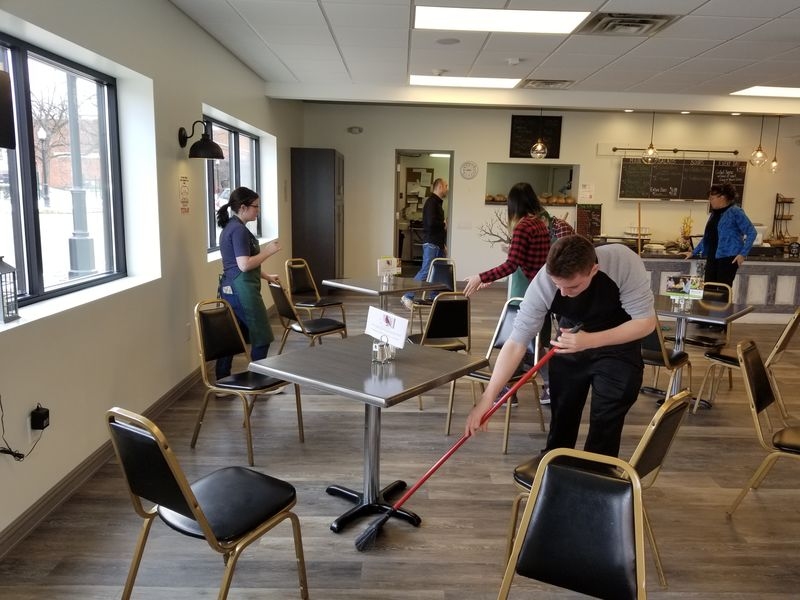 Students sweep floors and clean area of Knead Cafe