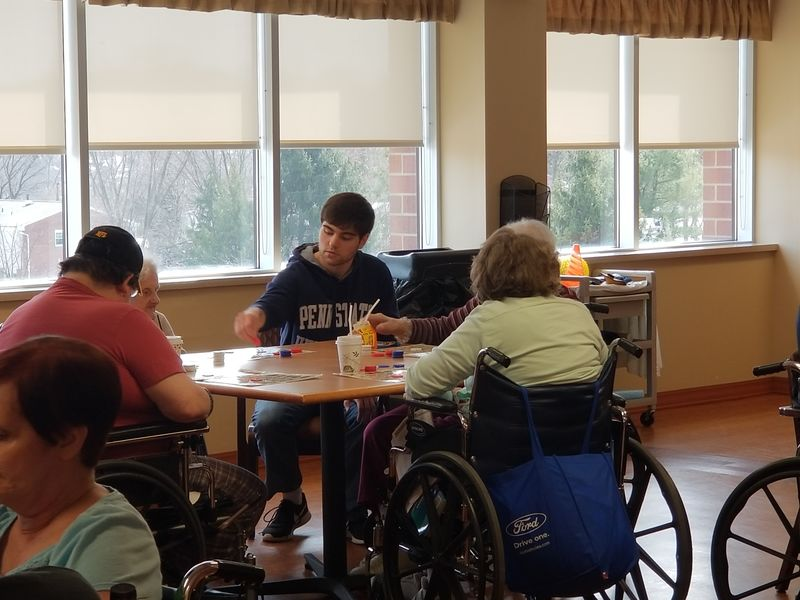 New Kensington student sits at table with Seneca Place residents to play Bingo
