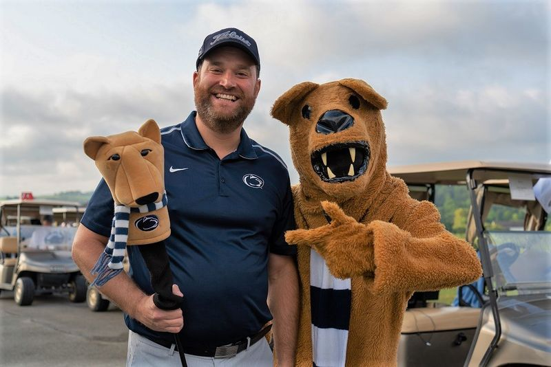 Man stands next to Nittany Lion mascot