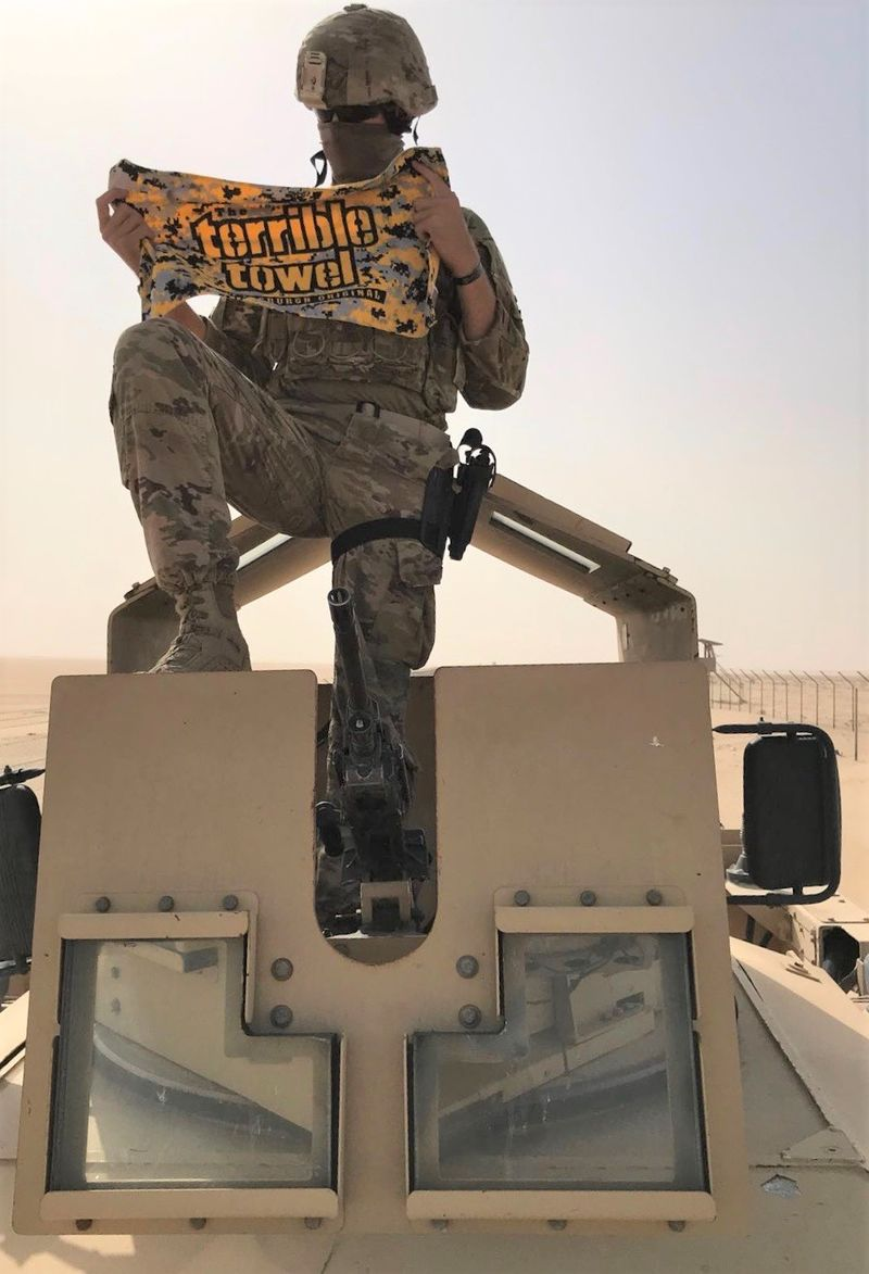 Man sits on M-ATV tank in desert holding Pittsburgh Terrible Towel