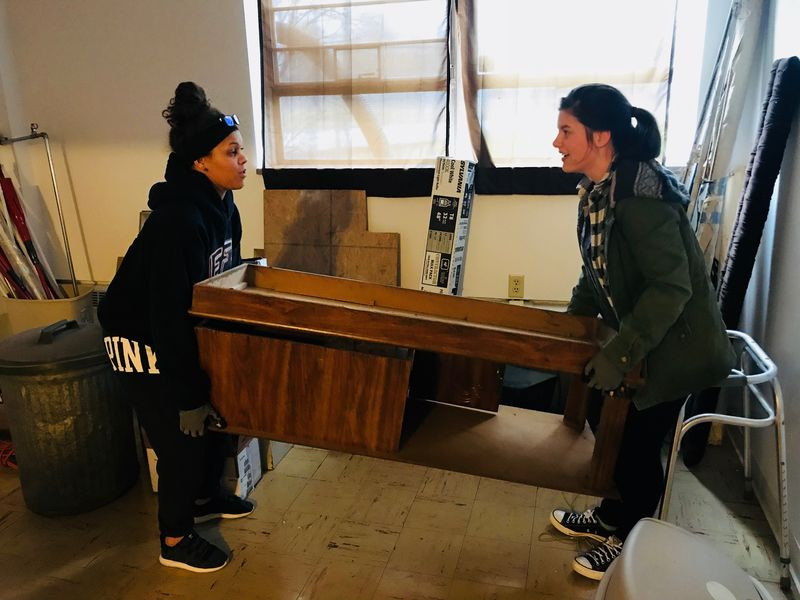 Two students carry table during community service project at local animal shelter