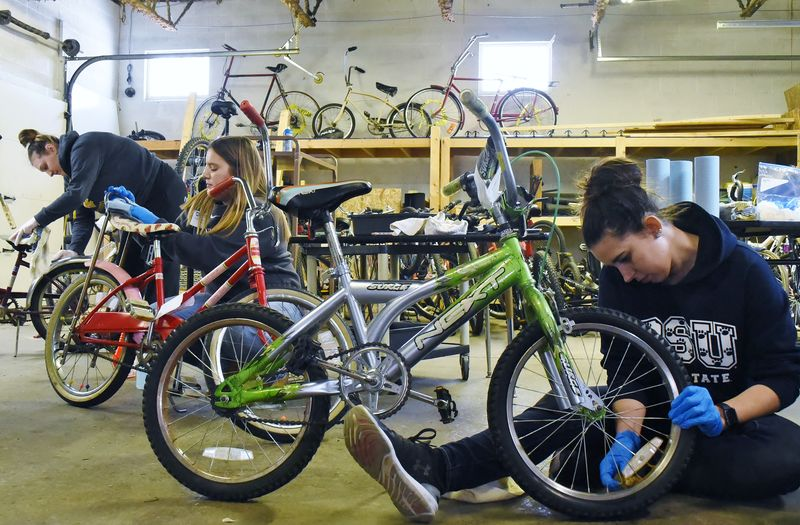 Three Penn State students repair bicycles at the Sisters of St. Joseph Neighborhood Network bike warehouse.
