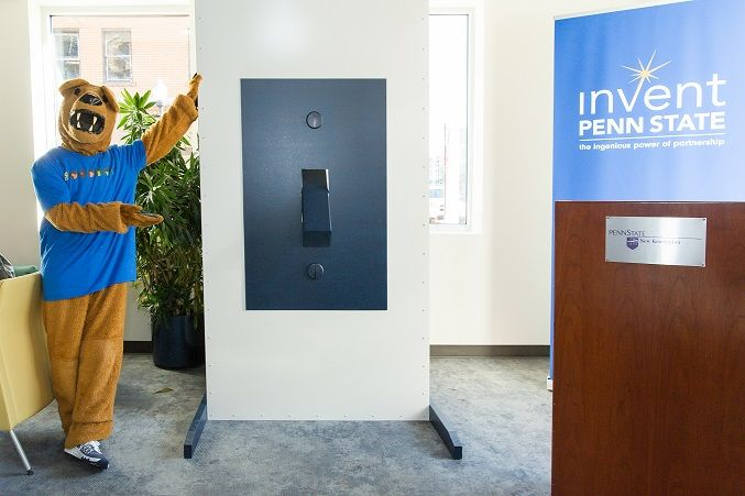 The Nittany Lion stands next to the light switch at The Corner entrepreneurial center