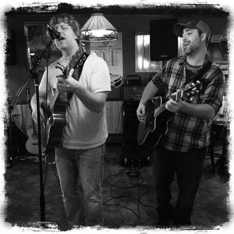 Two men playing guitar and singing