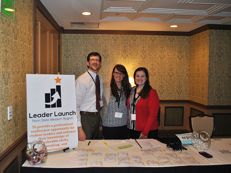 Three campus staff standing at the Leader Launch registration table