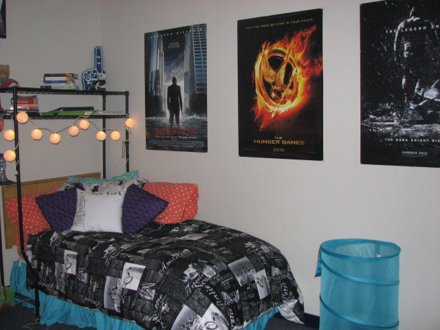 A bedroom with a bed and posters on the wall.