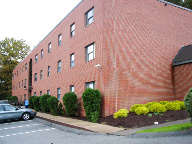 The red brick building exterior and well maintained landscaping