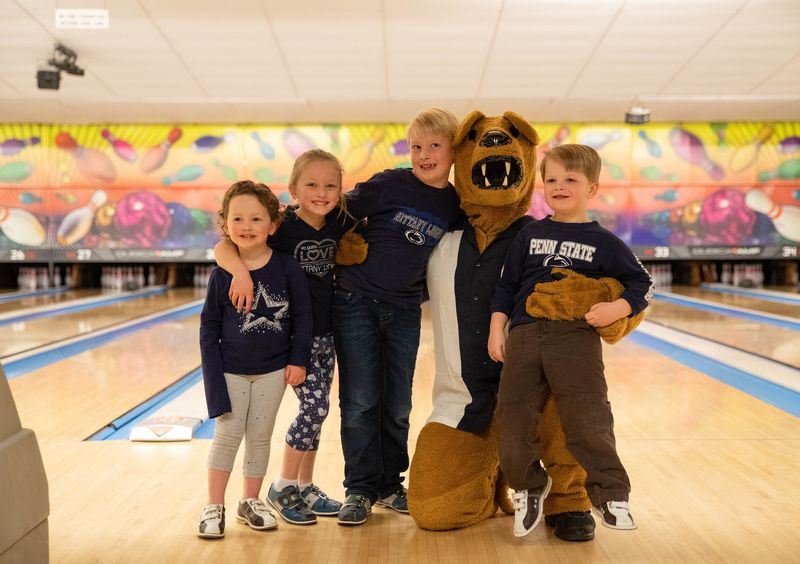Two young boys and girls stand with Nittany Lion mascot at bowling alley