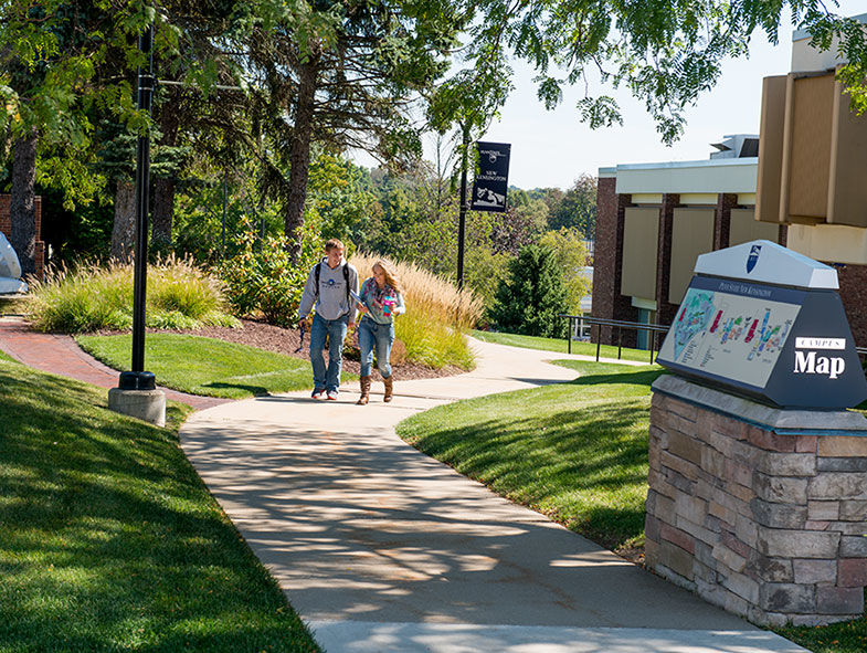 Two students walking on the campus grounds