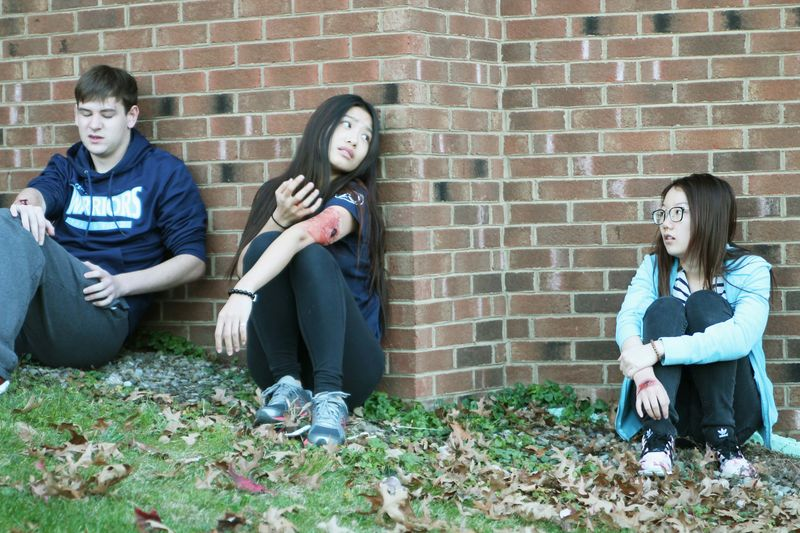 "Three ""wounded"" students sit against the wall during an active shooter exercise at Penn State Beaver"